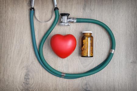 proteccion: Vista de arriba de un estetoscopio, un vaso de pastillas y un corazón rojo