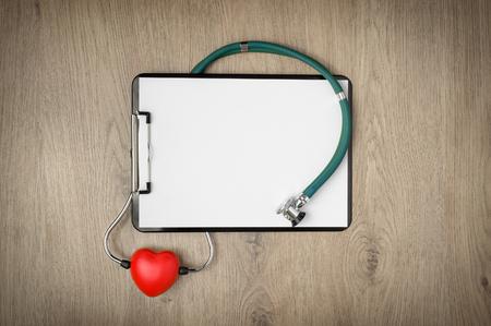 cheque en blanco: Portapapeles con papel blanco, estetoscopio y la forma del corazón en fondo de madera