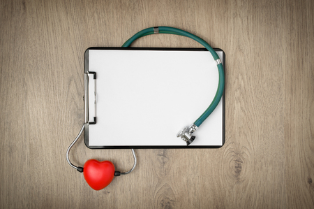 Clipboard with blank white paper, stethoscope and heart shape on wooden background