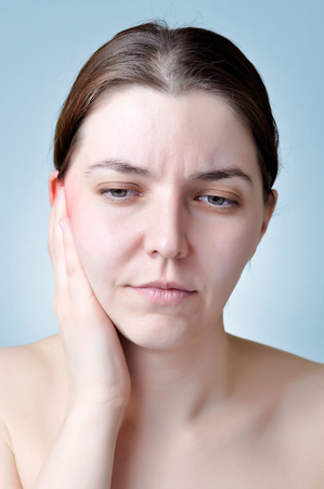 inflamed: Young woman touching her inflamed ear
