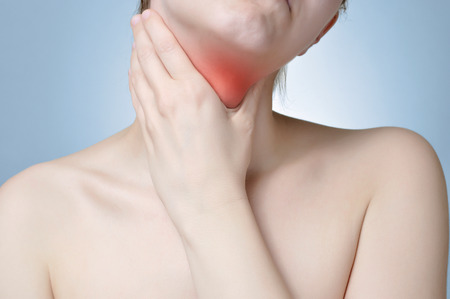 pharyngitis: Young woman holding her painful neck