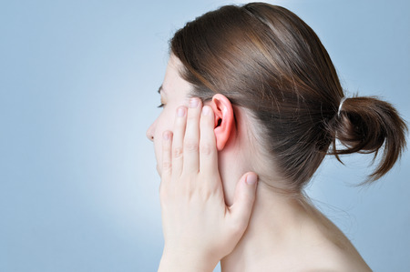 Young woman touching her inflamed ear photo