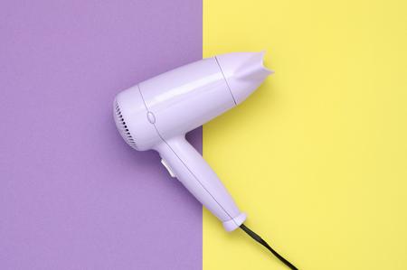 secador de pelo: secador de pelo morado sobre fondo de papel morado y amarillo