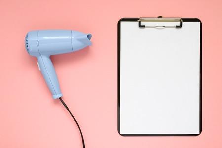 Blauw föhn en klembord op roze papier achtergrond