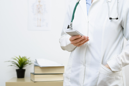 A female doctor texting on smartphone in medical office