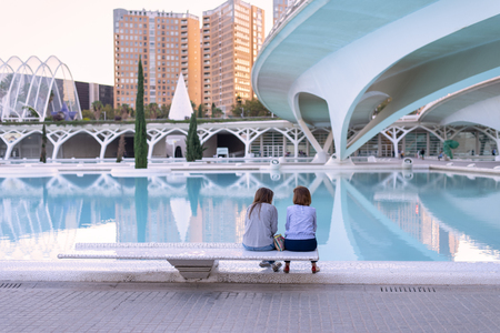 Valencia, Spain - 10 October, 2018: Two women chatting on a bench at the City of Arts and Sciences