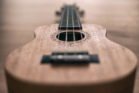 Brown ukulele on wooden background with shallow depht of field Banco de Imagens