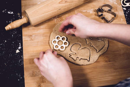 Top view of womans hands making gingerbread