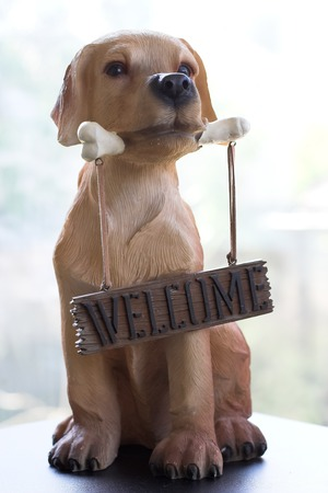 frequent: Dog holding a bone on which hangs a sign saying Welcome