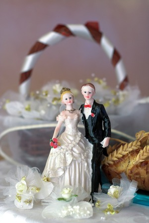 topper: top of wedding cake with bride and groom who hold hands Stock Photo