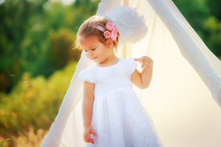 A little girl is standing by the white hut to nature