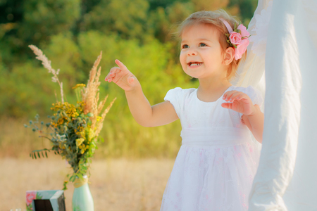 Little girl smiles and shows finger upward. A girl in a white Wigwam or play tent, childrens play house Stock Photo