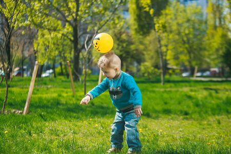 little boy is playing ball in the clearing. Above the childs head is a ball with a painted smile. Child on background of grass and trees. Stock Photo