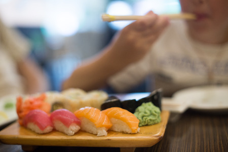 Boy eating sushi with chopsticks. Sushi Cafe.