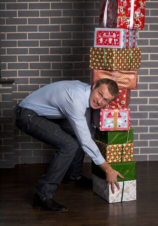 A man raises a stack of boxes with gifts. The man grimaced as he picked up the heavy boxes. Banco de Imagens