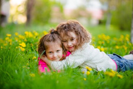 The older maidens hug the younger lying in dandelions. Sibling on a walk. Girls on a glade in the spring.