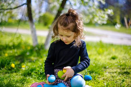 The girl is holding a collection of colorful Easter eggs. Stock Photo - 133182709