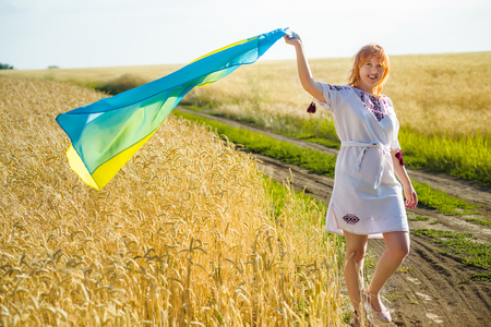 Flag Ukraine in hand girl in embroidered, national Ukrainian dress . Woman carries fluttering blue and yellow flag of Ukraine against background field of golden yellow ripe wheat. Stock Photo