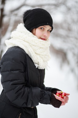 beautiful teenage girl in a black jacket and hat, with a white scarf, is holding two red Christmas-tree toys in her hands. A child dresses a Christmas tree on the street. A child in the background of a snow-covered city.