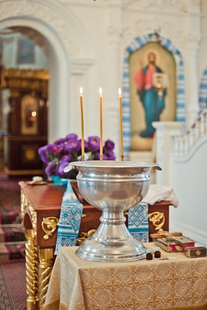 font for the baptism of an infant with burning candles. Interior Of Orthodox Church In Easter. baby christening. Ceremony a in Christian . bathing the into the baptismal font. Soft focus