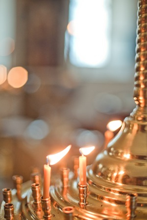 Candles in chandelier. Interior Of Orthodox Church In Easter. baby christening. Ceremony a in Christian . bathing the into the baptismal font. Soft focus