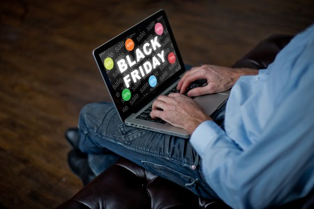 man buys online on Black Friday. man with a laptop, an adult mans hands on keyboard. Sale in Black Friday.