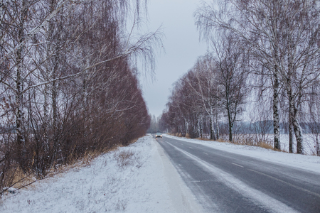 Snow-covered road with birches without foliage. Car on a slippery road. rolled track on first snow. Danger of drifts. Included lights on a white passenger car on winter time on the road. Glowing lights in a white passenger car winter time on the road Фото со стока