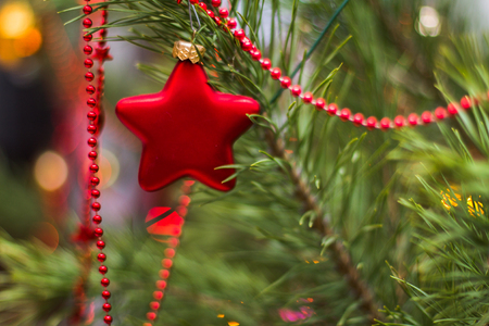 Red toy in the form of a star on a New Year's fir
