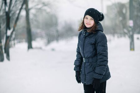 Teen girl froze. The child warms, hands clasped to his face. Portrait of a beautiful girl. Girl in black clothes Zdjęcie Seryjne