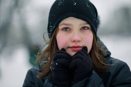 The girl is holding her hands in front of her face. Child with pink cheeks from frost.