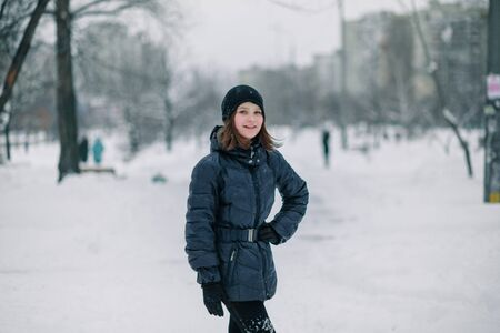 A girl with a hand on her belt. A child on a snow-covered road in the city. City after snowfall. Zdjęcie Seryjne