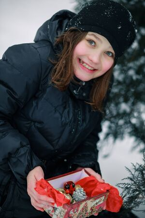 The girl is smiling happily by opening a gift. The child found a gift under the New Year fir on the street. Christmas open air.