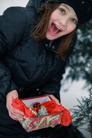 The girl screams with happiness revealing the gift. The child found a gift under the New Year fir on the street. A birth in the open air.