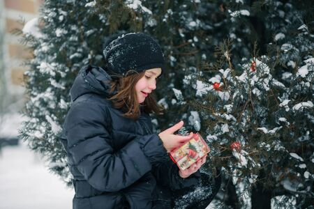 The girl found a gift under the tree and represents what is inside the box. A child with a gift. New Year. A box with a gift for Christmas. Zdjęcie Seryjne