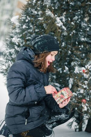The girl found a gift under the tree and represents what is inside the box. A child with a gift. New Year. A box with a gift for Christmas. Banco de Imagens