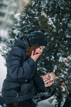 The girl is very surprised to see that in the gift box. The child found a gift under a tree in the street. Snow in the city. Zdjęcie Seryjne