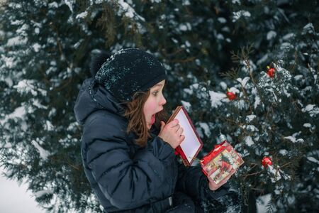 The girl opens a red box with a gift. The child found a gift under a tree in the street. Snow in the city. Zdjęcie Seryjne