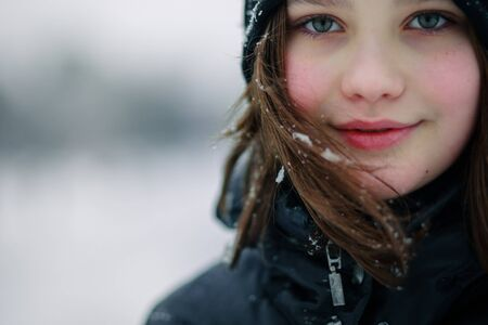 Portrait of a beautiful teenage girl with long hair. Girl in hat on the background of winter landscape.