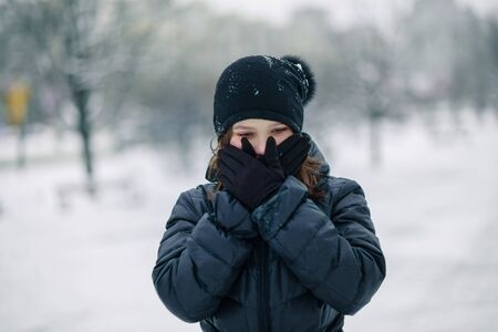Portrait of surprised girl covered her mouth with gloves. girl made a gesture, silence. A child walks after school on street in snowfall. Copy space Zdjęcie Seryjne