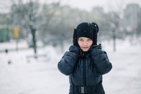 The girl covered her mouth with gloves. The girl made a gesture, silence. A child walks after school on the street in a snowfall. Copy space Zdjęcie Seryjne