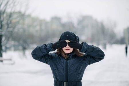 Girl decade closed eyes with his handst background of winter landscape. child does not want to look. Copy space