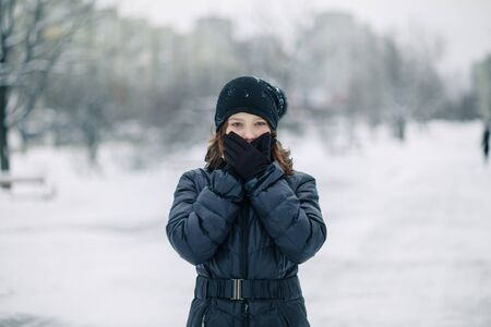 Portrait of surprised girl covered her mouth with gloves. girl made a gesture, silence. A child walks after school on street in snowfall.