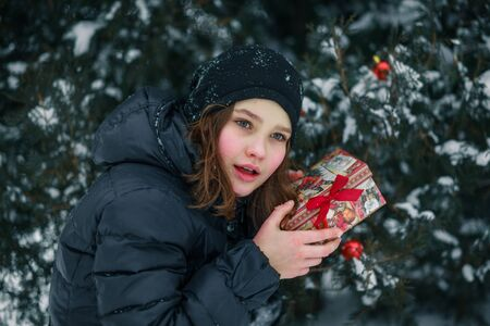 girl found a gift. A child with a gift. New Year. A box with a gift for Christmas.