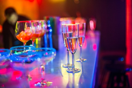 Bocals hanging on the bar. Wine glasses in a restaurant at a party. Light music and laser show in a bar or cafe.