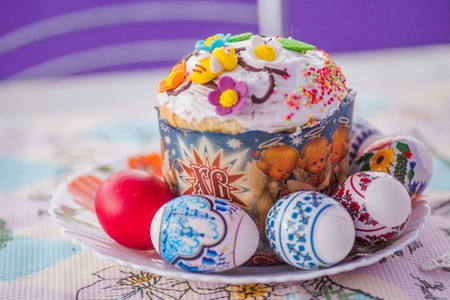 Hand-baked Easter cake on a plate next to decorated eggs. Eggs with stickers for Easter. Easter cake in a paper cookie cutter decorated with sugar flowers. Stok Fotoğraf