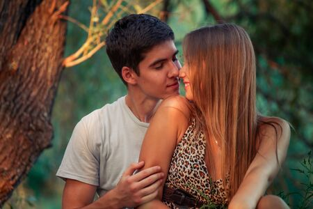 Handsome young man with dark hair kisses girl with long blond hair. Couple in love near tree. guy loves girl. Zdjęcie Seryjne