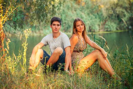 Couple boy and girl teenagers holding hands. The guy loves the girl. Young lovers sit on the shore of the lake near the tree. Zdjęcie Seryjne