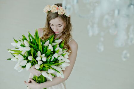 lovely girl hold in her hands bouquet of flowers of tulips. gift to woman for holiday for Womens Day. Happy bride. Valentines Day. March 8th Beautiful girl smiling. Zdjęcie Seryjne