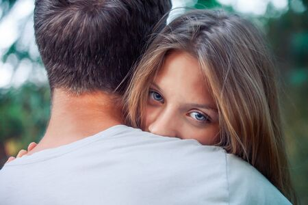 girl with beautiful blue eyes hugs boy. Happy lovers. woman with long hair looks out from behind mans shoulder. weak woman trusts man. Valentines Day.