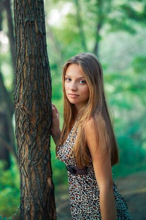 Beautiful girl standing by the tree. A lonely girl is waiting for a gift. Dangerous walk in the forest.